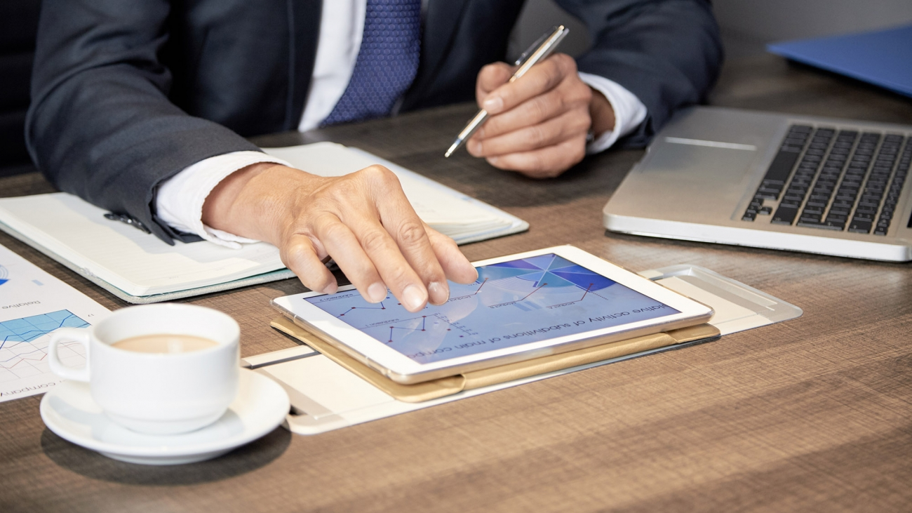 Faceless shot of anonymous formal man sitting at table in office with papers and using tablet
